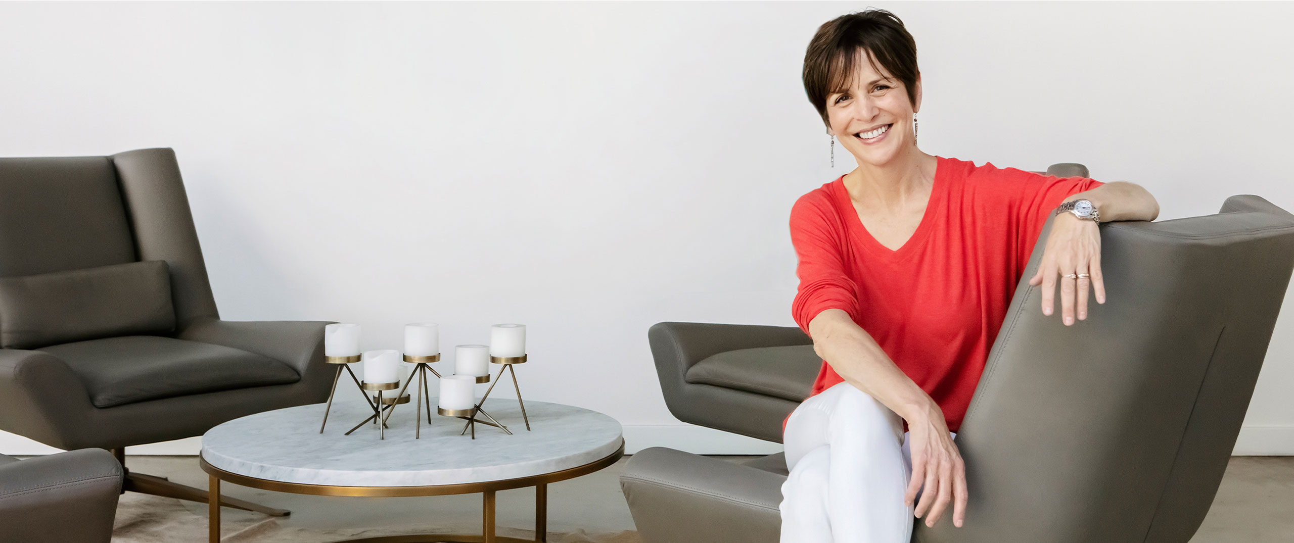 Linda Goldman sits smiling in a grey chair near a coffee table with candles on it