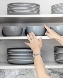 Hands placing dishes on an overhead shelf