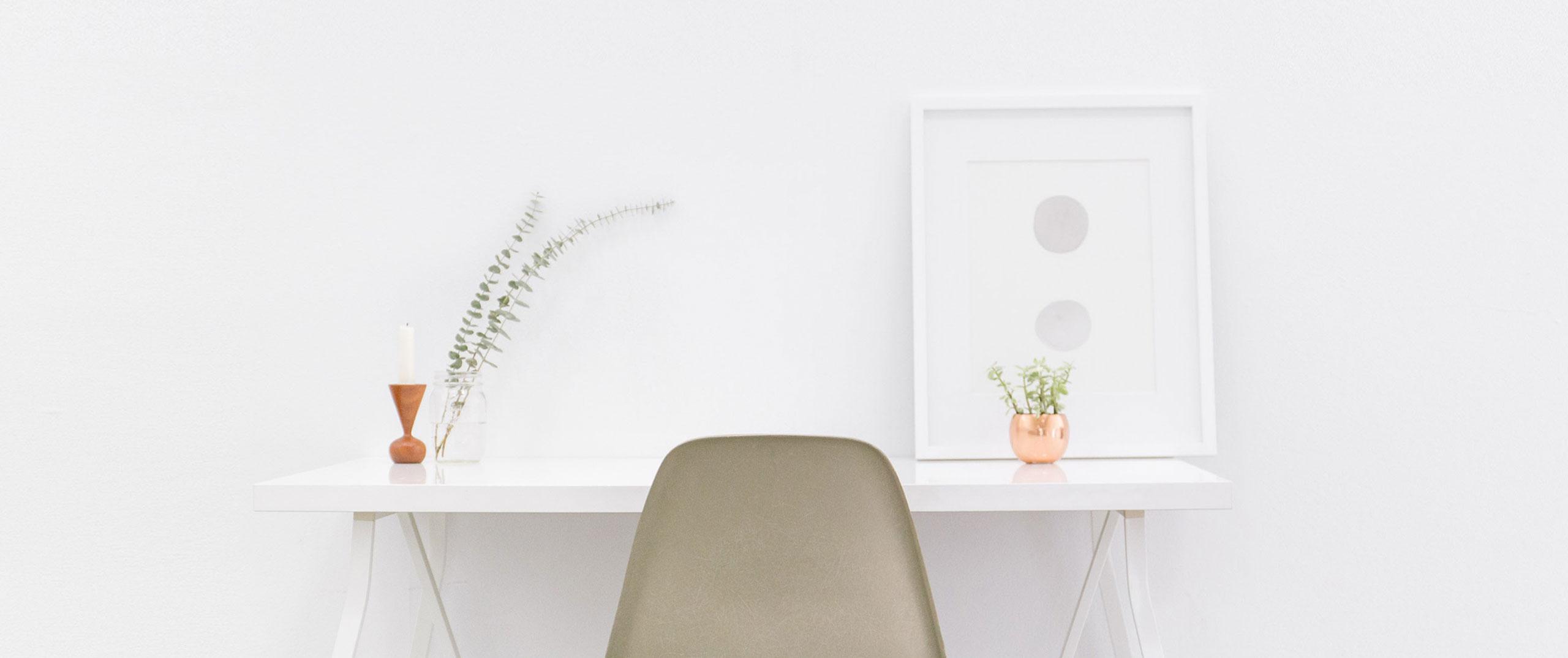 A clean white desktop with a modern beige chair
