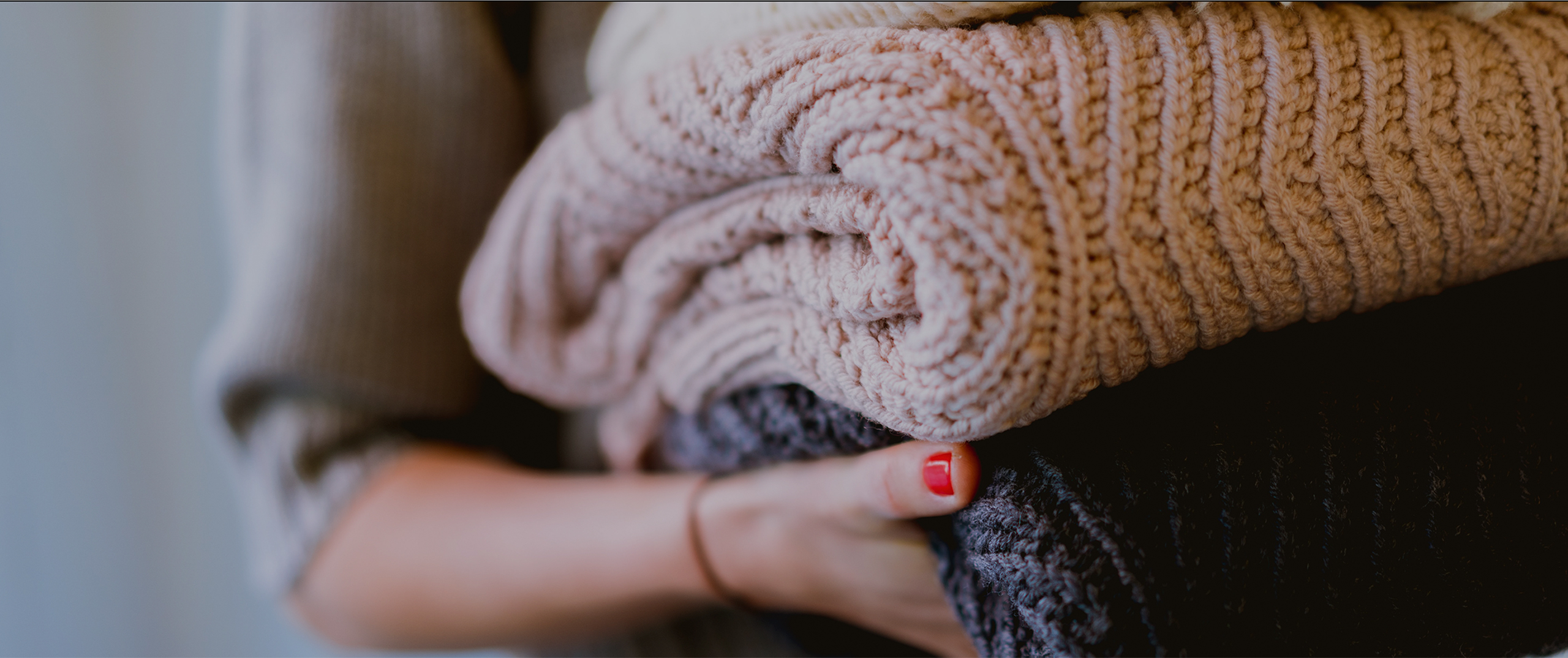 Female arms holding folded sweaters