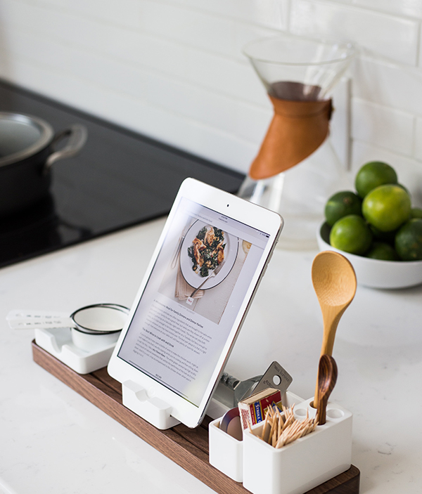 iPad in a holder with bowl of limes and decorative items on kitchen counter